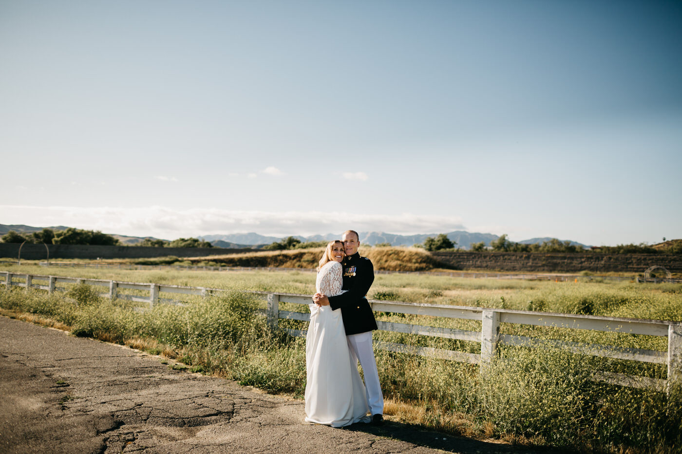bride and groom by fence