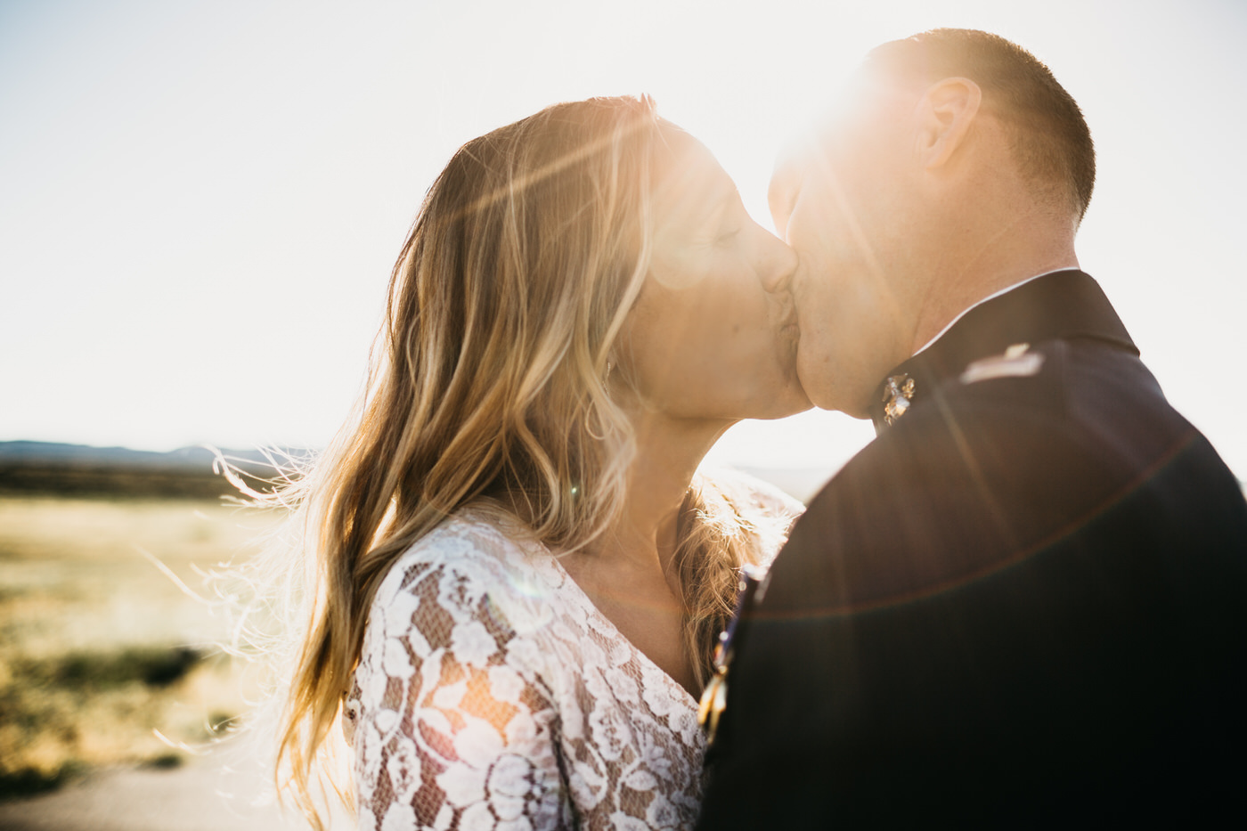 bride and groom kissing sun flare