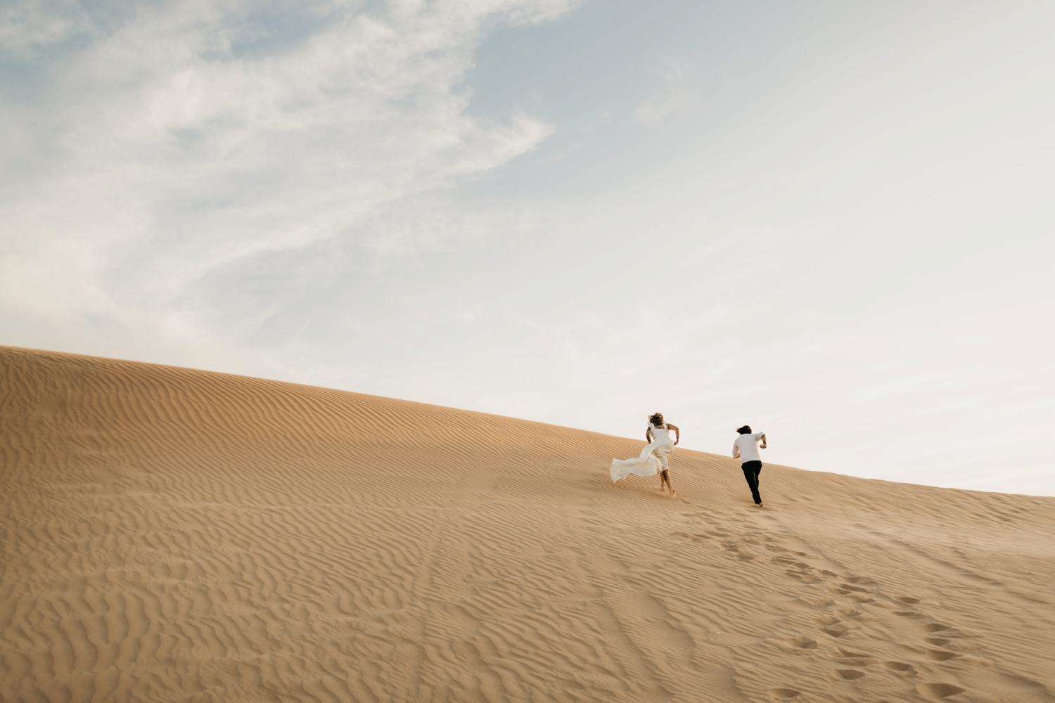 couple running in glamis sand dunes